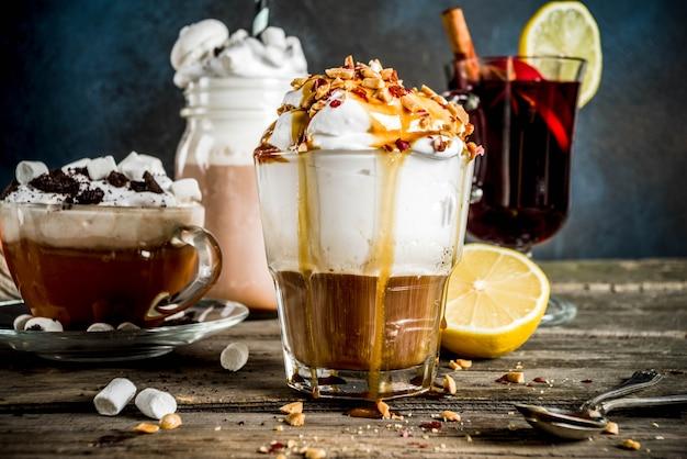 秋冬の暖かい飲み物、ホットチョコレート、カボチャラテ、キャラメルとピーナッツコーヒーラテ、グリューワイン、居心地の良い暗い背景 Premium写真