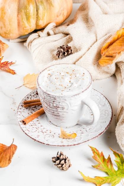 Осенние горячие напитки. тыквенный латте со взбитыми сливками, корицей и анисом на белом мраморном столе, со свитером (одеялом), осенними листьями и еловыми шишками. копировать пространство Premium Фотографии