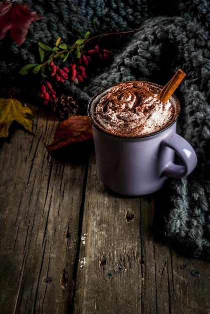 Осенние напитки, горячий шоколад или какао со взбитыми сливками и специями (корица, анис), на старом деревенском деревянном столе, с теплым уютным одеялом, сенной ягодой и листьями, копией пространства Premium Фотографии