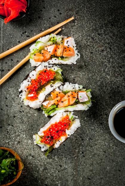 トレンドハイブリッド食品。日本アジア料理。ミニ寿司タコス、サーモンのサンドイッチ、林わかめ Premium写真