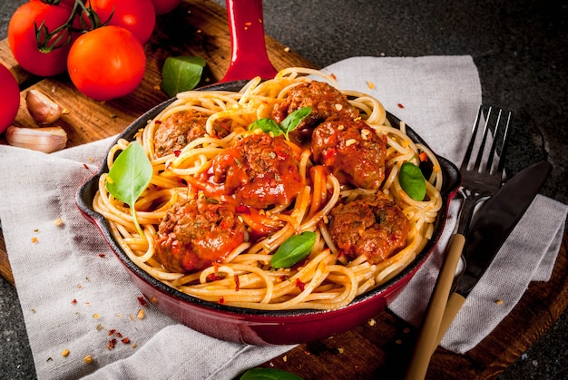 ミートボールのスパゲッティパスタ、まな板と黒い石のテーブルの上の赤い鋳鉄パンのバジルトマトソース Premium写真