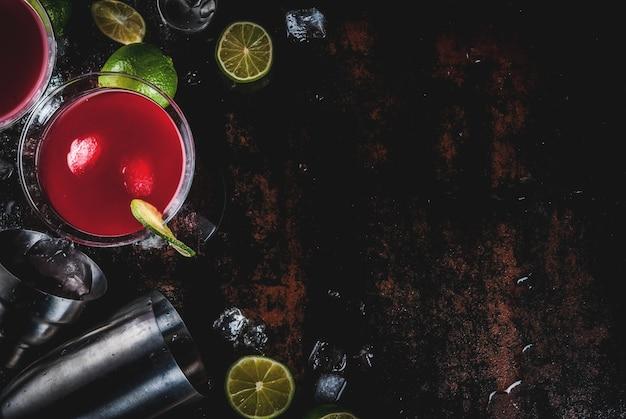Красный космополитичный коктейль с лаймом в бокале для мартини, на темной ржавой сцене Premium Фотографии