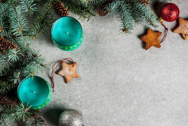 Рождественский стол, для поздравительной открытки. украшение рождества, свечи, ель и пряники на сером каменном столе. вид сверху, . Premium Фотографии