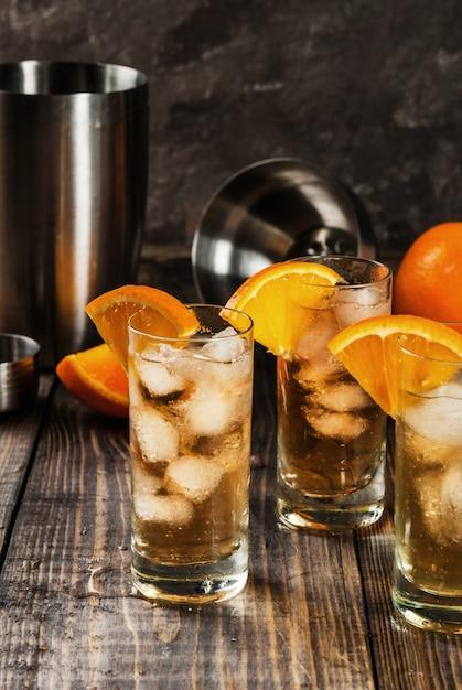 アルコールウォッカウイスキーオレンジハイボールカクテル、オレンジの飾り、木製のテーブルの上 Premium写真