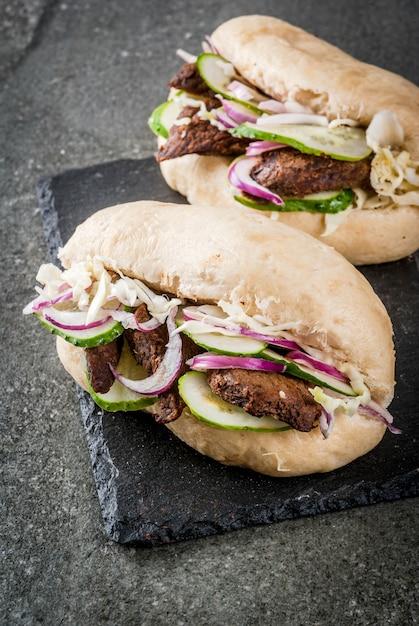 サンドイッチ。ファストフード。豚肉、牛肉、新鮮な野菜、ホットソースを詰めた伝統的な中国のアジアのバオパン。暗い石のテーブルの上。 Premium写真