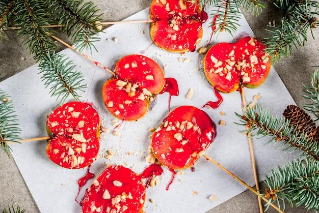 Идеи зимы, рождественские угощения. сладости для детей. шоколадное яблоко ломтики красной карамели и орехов. серый каменный фон, с еловыми ветками, вид сверху Premium Фотографии
