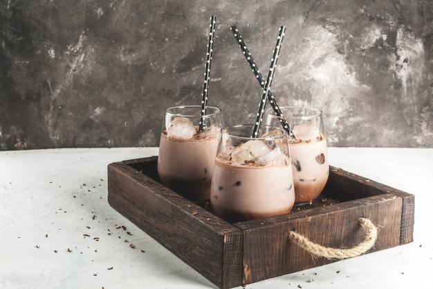 夏の飲み物。チルドアイスチョコレートココア。チョコレートアイスクリーム、チョコレートパウダー、アイススクープ。グラス、飲み用チューブ付き。白いコンクリートテーブル木製トレイ。 Premium写真