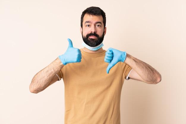 善と悪のサインを作る壁の上のマスクと手袋で保護するひげを持つ白人男 Premium写真