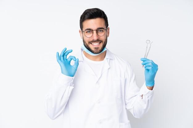 Инструменты дантиста держа на белой стене показывая одобренный знак с пальцами Premium Фотографии
