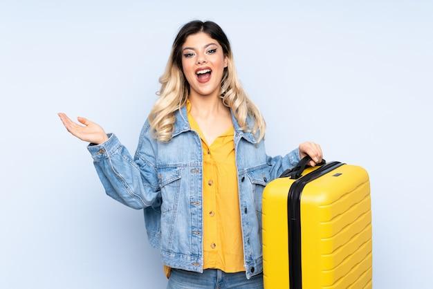 Путешественник подросток держит чемодан на синей стене в отпуск с чемоданом путешествия и удивлен Premium Фотографии