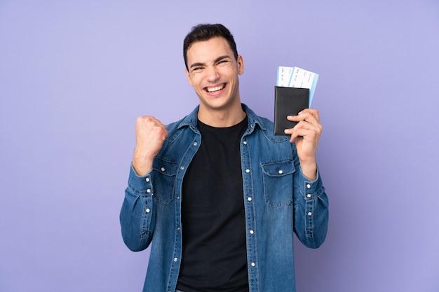 Молодой кавказский красавец на фиолетовой стене счастливы в отпуске с паспортом и билетами на самолет Premium Фотографии