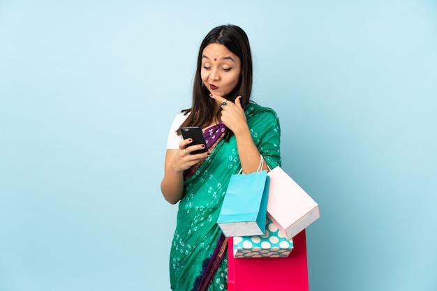 思考とメッセージを送信する買い物袋を持つ若いインド人女性 Premium写真