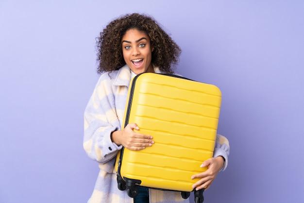 Молодая афро-американская женщина на фиолетовой стене в каникулах с чемоданом перемещения и удивленная Premium Фотографии