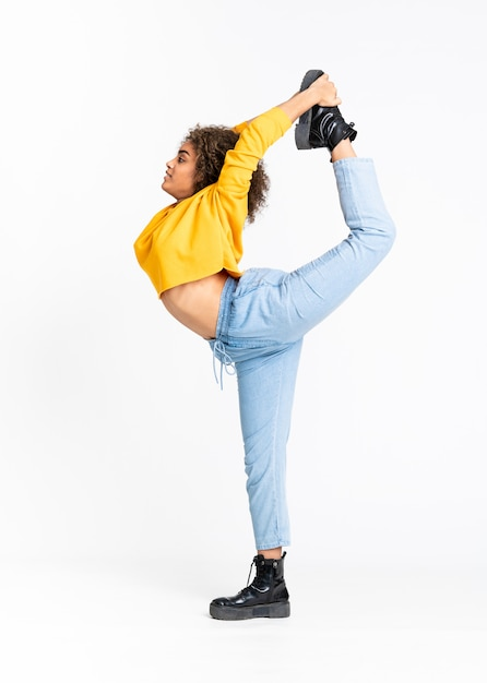 白い壁を越えて踊る若いアフリカ系アメリカ人女性 Premium写真
