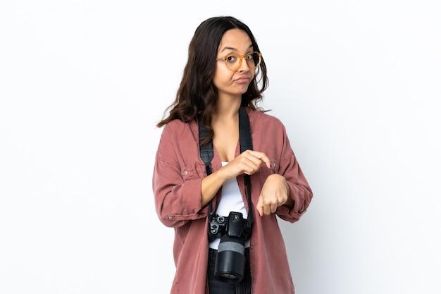 Молодой фотограф женщина над белой стеной, делая жест опоздания Premium Фотографии