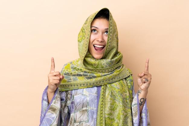 Индийская женщина, изолированных на бежевом удивлен и направлен вверх Premium Фотографии