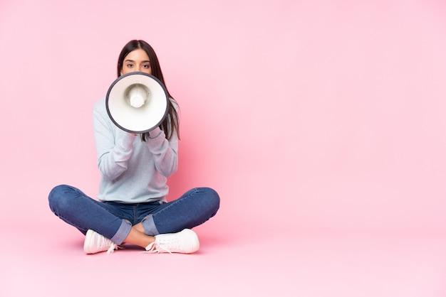 Молодая кавказская женщина изолированная на пинке крича через мегафон Premium Фотографии