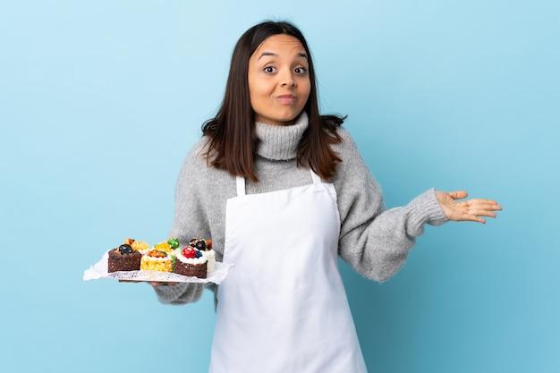 疑いのジェスチャーを作る孤立した青い空間に大きなケーキを置くパティシエ Premium写真