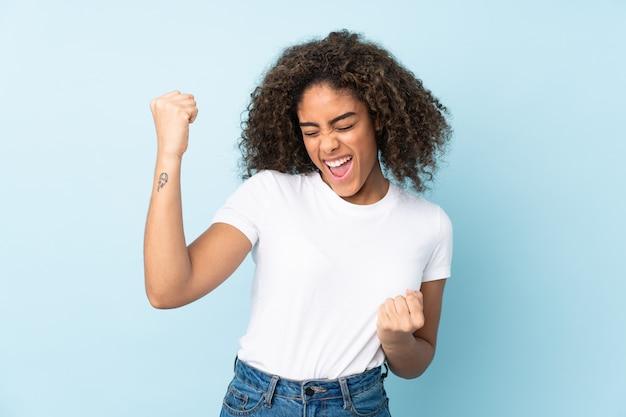 Молодая афро-американская женщина изолированная на сини празднуя победу Premium Фотографии