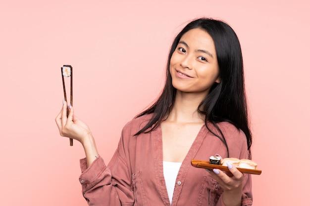Девушка подростка азиатская есть суши изолированные на пинке Premium Фотографии