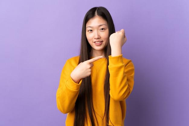 Молодая китайская женщина над изолированной фиолетовой стеной делая жест опоздания Premium Фотографии