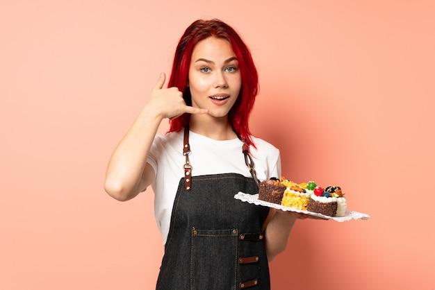 Шеф-кондитер держа булочки изолированные на розовой стене делая жест телефона. перезвони мне знак Premium Фотографии
