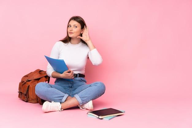 Девушка студента подростка кавказская сидя на поле изолировала на пинке слушая к что-то путем кладущ руку на ухо Premium Фотографии