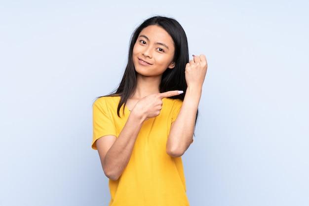 Женщина подростка изолированная на сини делая жест опоздания Premium Фотографии