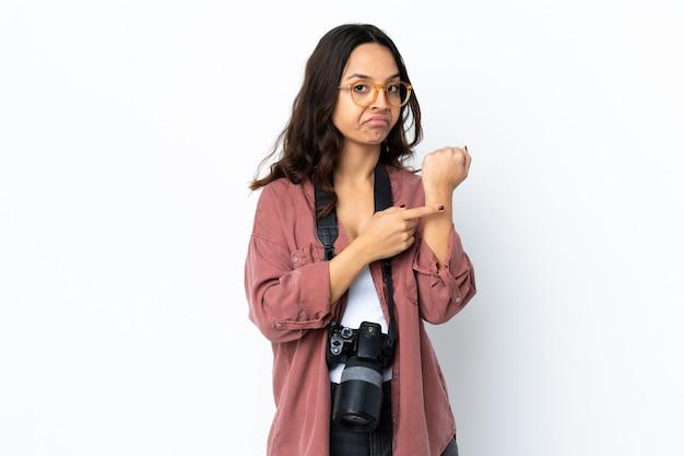 Молодая женщина фотографа над изолированной белизной делая жест быть поздно Premium Фотографии