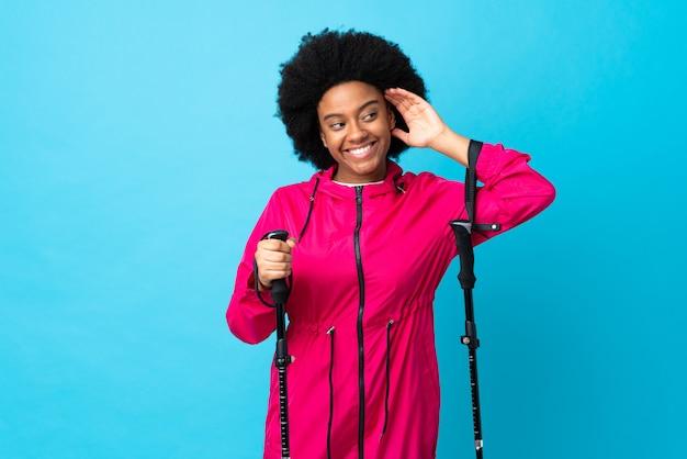 Молодой афроамериканец с рюкзаком и треккинг полюсов, изолированных на синем фоне, слушая что-то, положив руку на ухо Premium Фотографии
