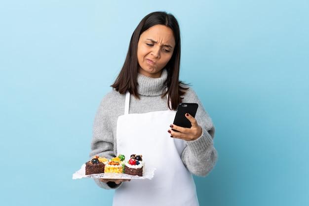 Шеф-кондитер держит большой торт над синей стеной, думая и отправляя сообщение Premium Фотографии