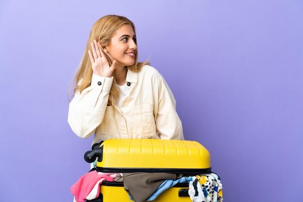 Молодая уругвайская белокурая женщина с чемоданом, полным одежды над изолированной фиолетовой стеной, слушает что-то, кладя руку на ухо Premium Фотографии