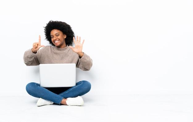 Молодая афро-американских женщина с ноутбуком, сидя на полу, считая семь с пальцами Premium Фотографии