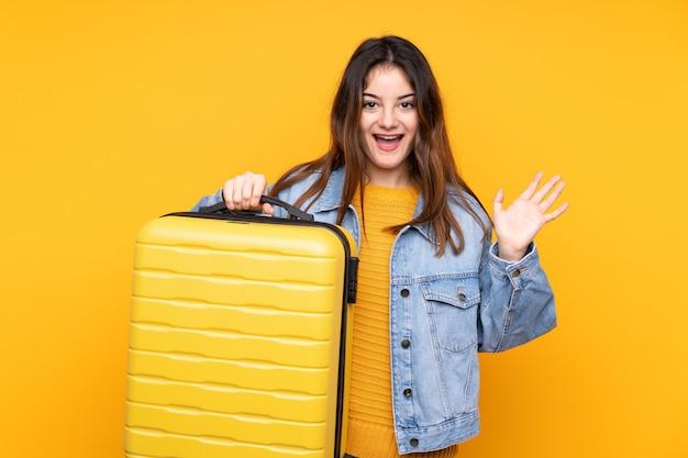 旅行スーツケースで休暇で黄色の壁に若い白人女性と驚いた Premium写真