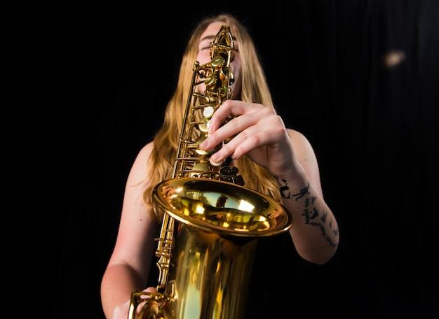 Девушка в бейсболке играет на саксофоне в студии звукозаписи
