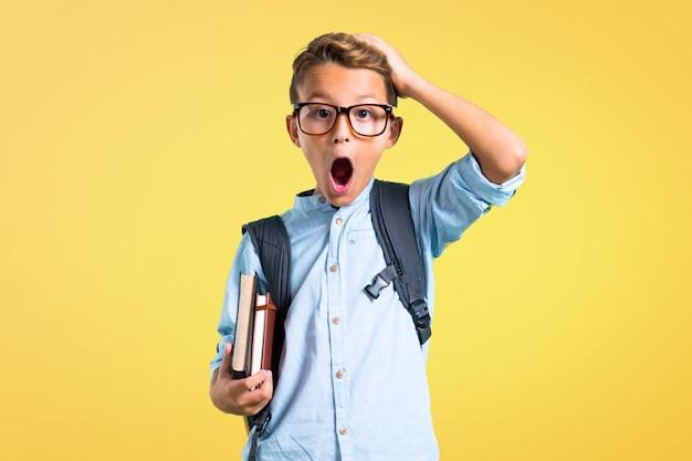 バックパックと眼鏡が不幸で何かに不満を持っている学生の少年。 Premium写真