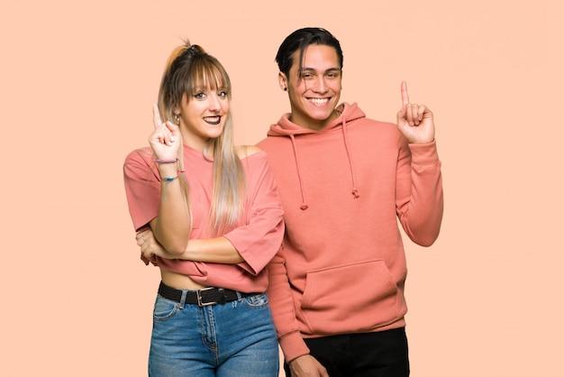 バレンタインの日に若いカップルを示すとピンクの背景の上の最高の印で指を持ち上げる Premium写真