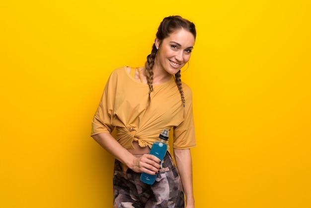 Спортивная женщина на ярком желтом фоне с бутылкой Premium Фотографии