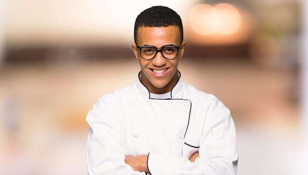 メガネとやり場のない背景に幸せな若いアフロアメリカンシェフ男 Premium写真