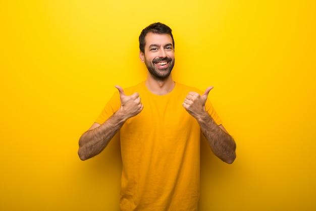両手で親指ジェスチャーを与えると笑みを浮かべて黄色の鮮やかな黄色の男 Premium写真