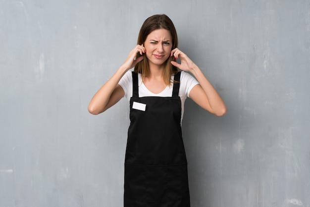 イライラして手で耳を覆っている従業員女性 Premium写真
