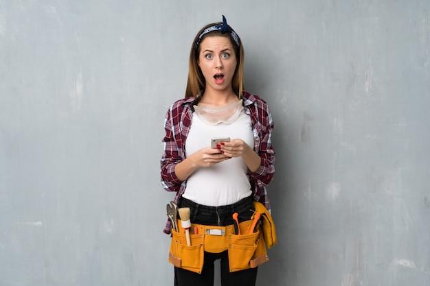職人や電気技師の女性が驚いてメッセージを送る Premium写真
