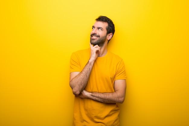 見上げながらアイデアを考えて孤立した鮮やかな黄色の色の男 Premium写真