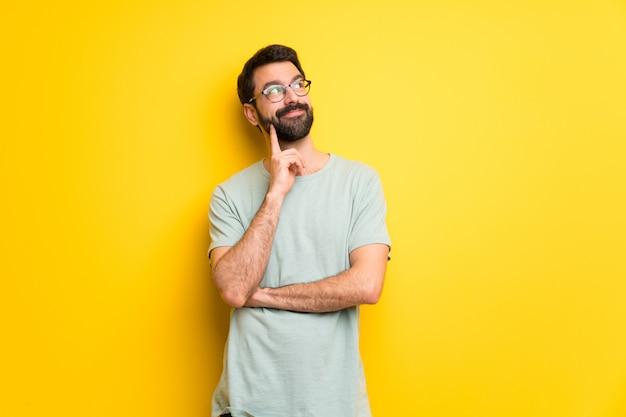 見ながらアイデアを考えてひげと緑のシャツを持つ男 Premium写真
