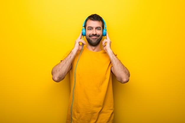 ヘッドフォンで音楽を聞いて孤立した鮮やかな黄色の色の男 Premium写真