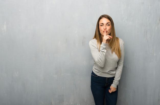 口の中に指を入れて沈黙ジェスチャーのサインを示すテクスチャ壁上の若い女性 Premium写真