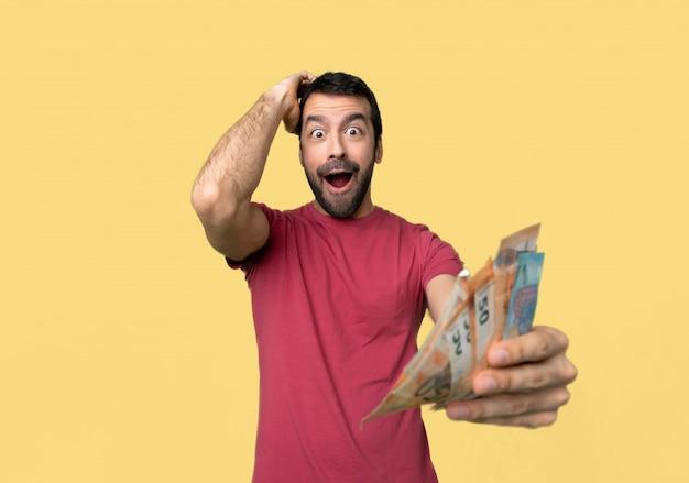 驚きとショックを受けた表情でたくさんのお金を取る人 Premium写真