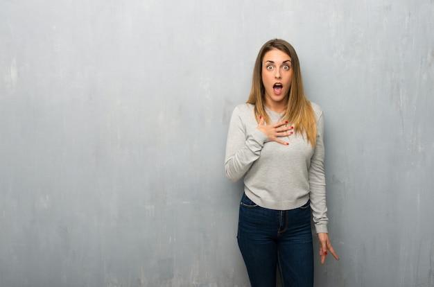 Молодая женщина на текстурированной стене удивлен и шокирован, глядя прямо Premium Фотографии