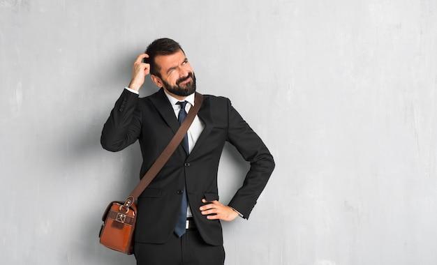 頭を掻きながら疑問を持ってひげを持ったビジネスマン Premium写真