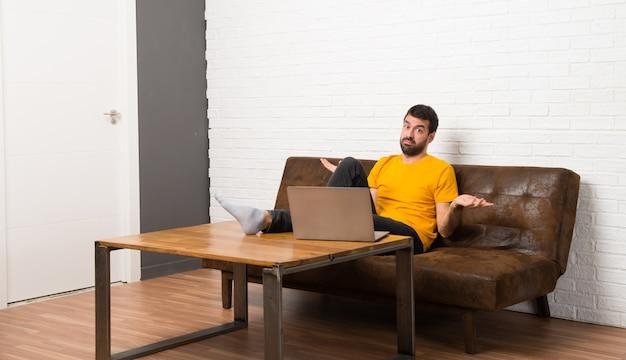 Человек с ноутбуком в комнате несчастлив и разочарован чем-то, потому что не понимает что-то Premium Фотографии